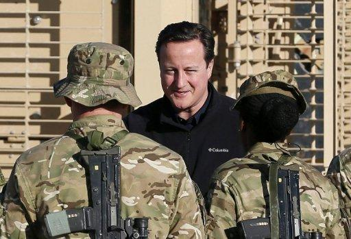British Prime Minister David Cameron (C) speaks with soldiers in Helmand Province, Afghanistan, on December 20, 2012
