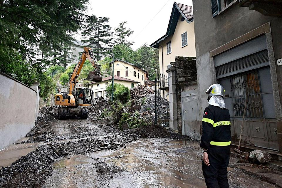 A fireman inspects damages caused by a landslide in Laglio, on July 28, 2021, after heavy rain caused floods in towns surrounding Lake Como in northern Italy.
