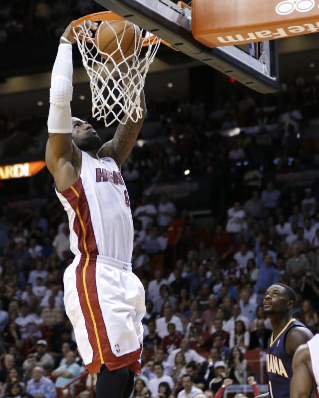 Miami Heat's LeBron James dunks as Indiana Pacers' Lance Stephenson watches during the second half of an NBA basketball game, Friday, April 11, 2014, in Miami. The Heat defeated the Pacers 98-86. (AP Photo/Lynne Sladky)