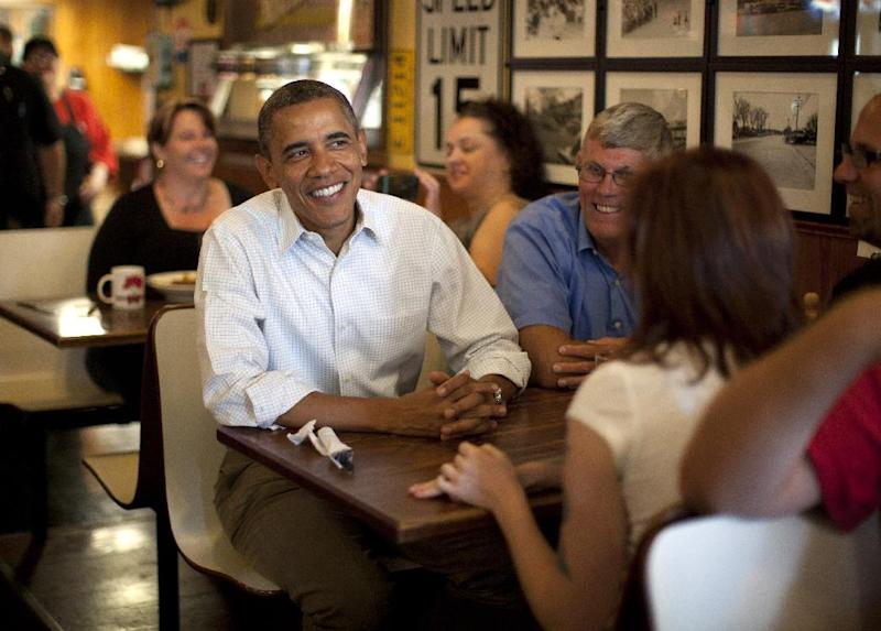 President Barack Obama has breakfast with three Iowa veterans, Amanda Irish, third from left back to camera, Jake Krapfi, far right, and Terry Phillips, second from left, at Riley's Cafe and Catering, Wednesday, Aug. 15, 2012, in Cedar Rapids, Iowa,  during a three day campaign bus tour through Iowa. (AP Photo/Carolyn Kaster)