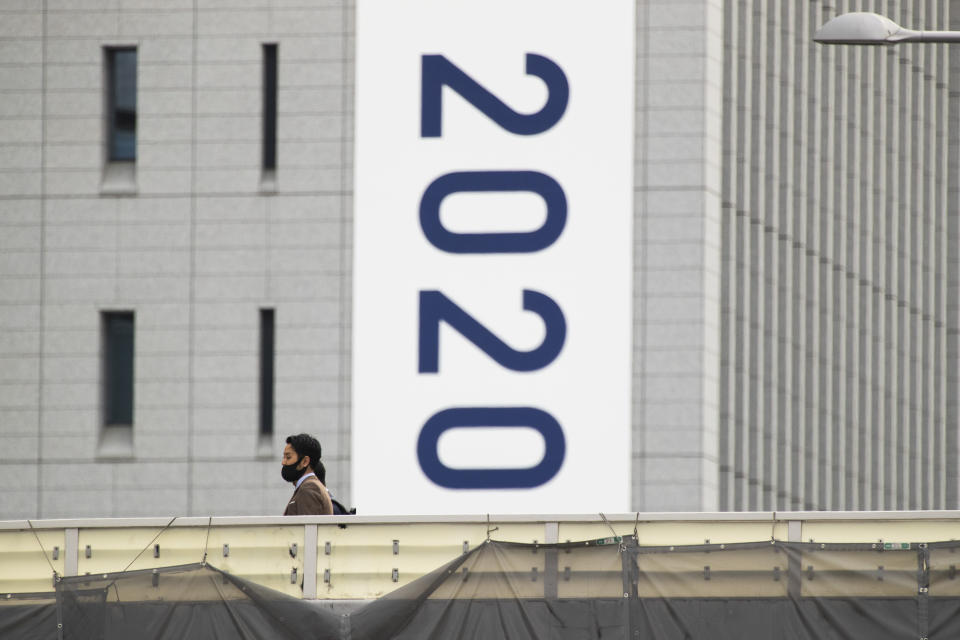 People wearing face masks walk on a crossover bridge near a banner to promote the rescheduled Tokyo 2020 Olympic Games in Tokyo Friday, April 2, 2021. Many preparations are still up in the air as organizers try to figure out how to hold the postponed games in the middle of a pandemic. (AP Photo/Hiro Komae)