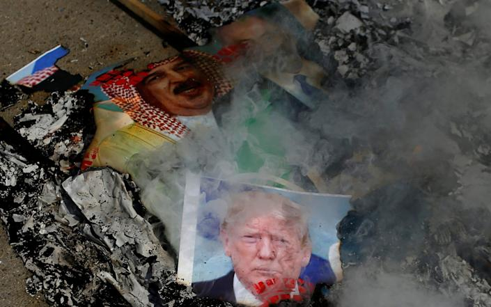 Pictures depicting U.S. President Donald Trump, Bahrain's King Hamad bin Isa Al Khalifa, and Israeli Prime Minister Benjamin Netanyahu are burnt by Palestinians during a protest against the United Arab Emirates and Bahrain's deal with Israel to normalise relations, in Gaza City - Reuters