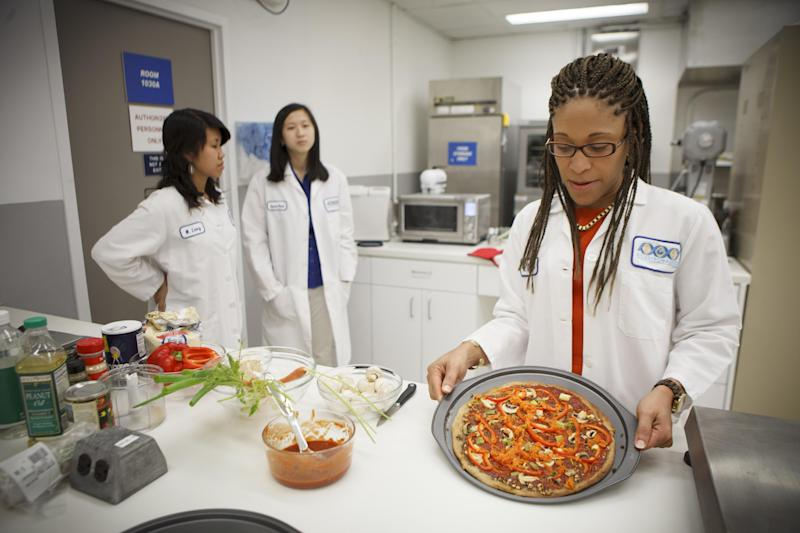 Lockeed Martin senior research scientist Maya Cooper shows a vegan pizza developed at NASA's Advanced Food Technology Project at Johnson Space Center in Houston Tuesday, July 3, 2012. NASA is currently planning a mission to Mars, which has gravity, so more options for food preparation, like chopping vegetables, are available as opposed to the dehydrated fare of current space missions. (AP Photo/Michael Stravato)
