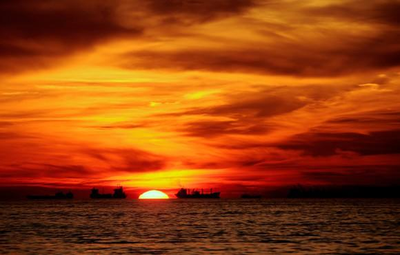 Tanker ships out on the water with an orange sunset in the background.