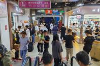 Shoppers look to pick up cosmetic products from wholesalers inside the Mingtong Digital City market in Shenzhen's Huaqiangbei area