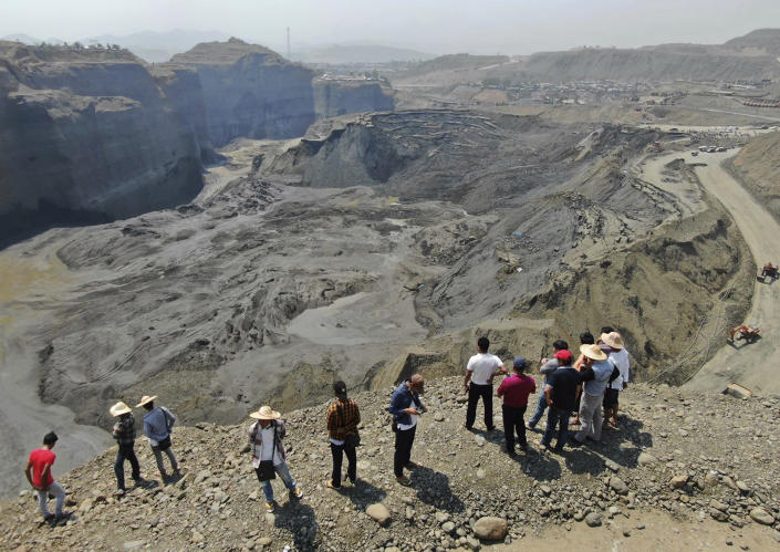 FILE - In this April 23, 2019, file photo, people stand atop a ridge overlooking the scene of a mudslide at a jade gemstone mining site in Hpakant area of Kachin state, northern Myanmar. U.S. sanctions on Myanma Gems Enterprise target an army-controlled gems business rife with corruption and abuses that is one of the junta's key sources of revenue. State-controlled Myanma Gems is a part of the Ministry of Mines, controls mining and marketing of jade and other gemstones, one of resource-rich Myanmar's most lucrative industries. (AP Photo/Zaw Moe Htet, File)