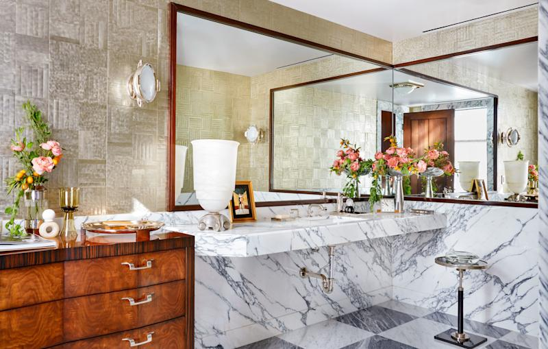 A metallic wall covering by Maya Romanoff brightens the powder room. Sconce by Thomas O'Brien for Visual comfort; custom sink and vanity of arabescato cervaiole marble; Waterworks faucet.