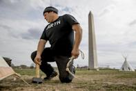 Aldo Seoane of the Yoeme tribe, with a group protesting the Dakota Access oil pipeline, helps set up teepees on the National Mall near the Washington Monument in Washington, Tuesday, March 7, 2017. A federal judge declined to temporarily stop construction of the final section of the disputed Dakota Access oil pipeline, clearing the way for oil to flow as soon as next week. (AP Photo/Andrew Harnik)