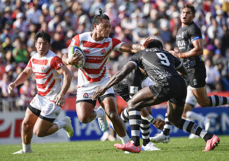 Japan's Lomano Lava Lemekicenter, center, fends off Fiji's Frank Lomani during a Pacific Nations Cup rugby match at Kamaishi Recovery Memorial Stadium in Kamaishi, northern Japan, Saturday, July 27, 2019. Japan took big step forward in Rugby World Cup preparation with a five-try 34-21 win over Fiji in Pacific Nations Cup (Tsuyoshi Ueda/Kyodo News via AP)