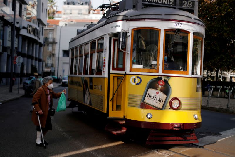 FILE PHOTO: A woman wearing a protective mask speaks with a driver of a tram during the coronavirus outbreak in Lisbon, Portugal