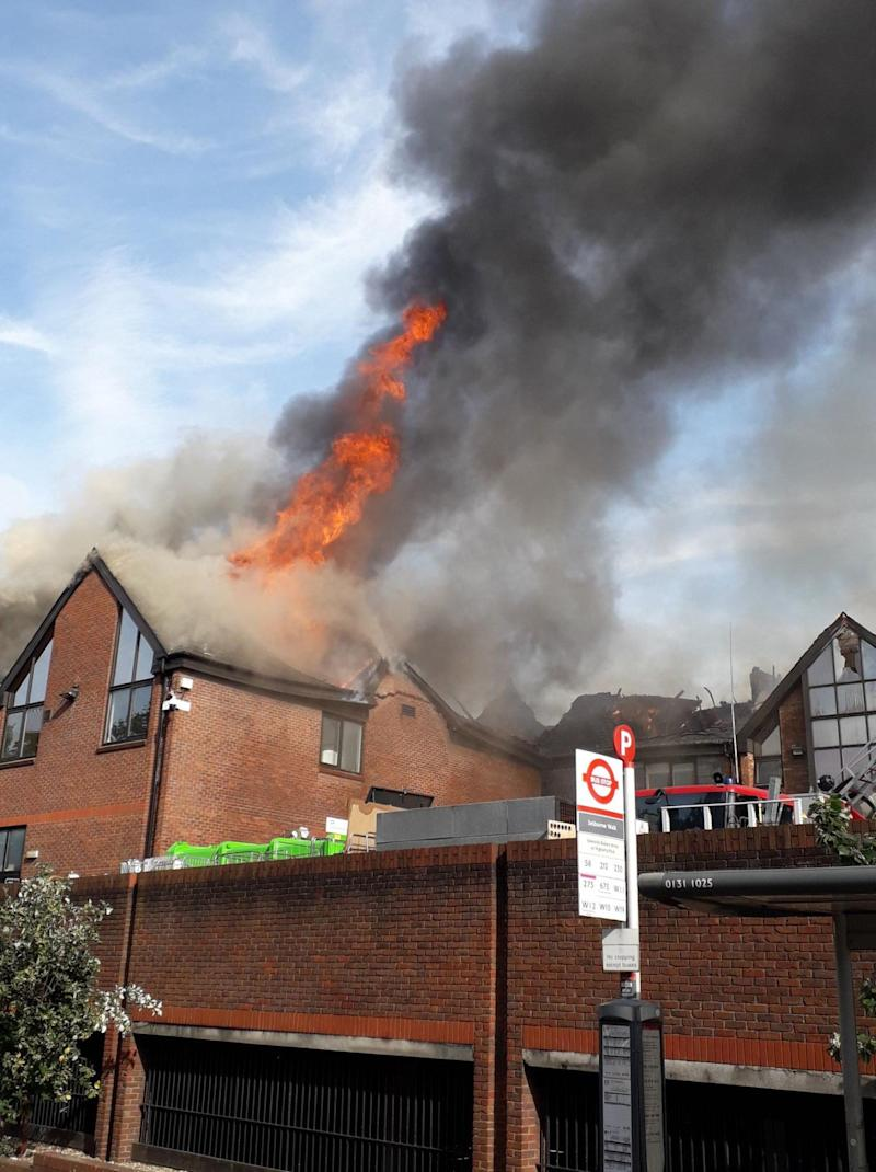 Flames rise from the roof of the shopping centre.