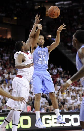 North Carolina forward J.P. Tokoto (25) passes the ball against Maryland forward Charles Mitchell (0) during the first half of an NCAA college basketball game on Wednesday, March 6, 2013, in College Park, Md. (AP Photo/Nick Wass)