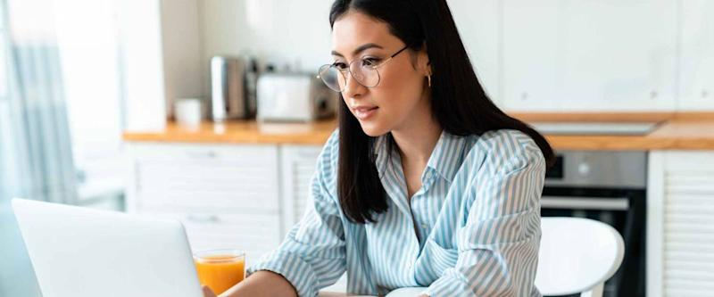Image of a beautiful concentrated brunette young woman at the kitchen indoors at home using laptop computer work.