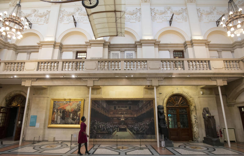 A passer-by views the painting 'Devolved Parliament' by the graffiti artist Banksy, which is going on show at Bristol Museum.