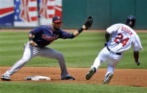 Minnesota Twins shortstop Pedro Floriman left, prepares to tag out Cleveland Indians' Michael Bourn (24 on a steal-attempt during the first inning of a baseball game in Cleveland, Sunday, June 23, 2013. AP Photo/Phil Long)