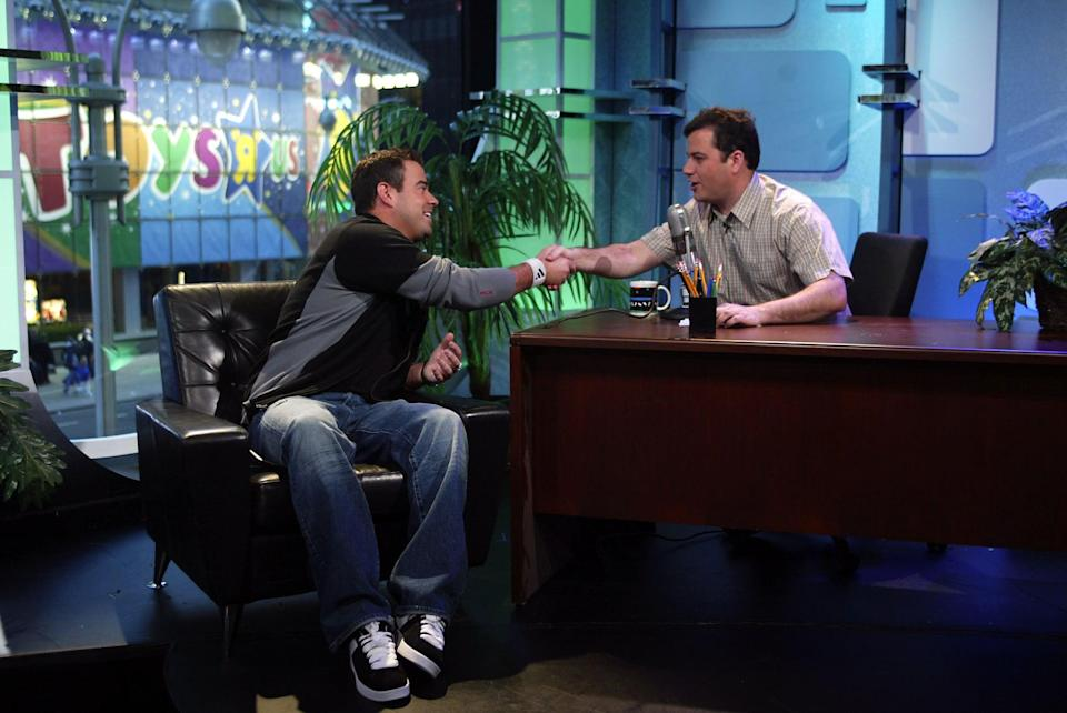 """<p>Jimmy Kimmel sat in a """"practice"""" late-night desk to interview Carson Daly on <b>TRL</b> in 2003.</p>"""