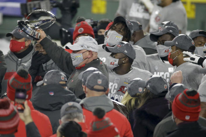 Tampa Bay Buccaneers head coach Bruce Arians holds the championship trophy after winning the NFC championship NFL football game against the Green Bay Packers in Green Bay, Wis., Sunday, Jan. 24, 2021. The Buccaneers defeated the Packers 31-26 to advance to the Super Bowl. (AP Photo/Mike Roemer)