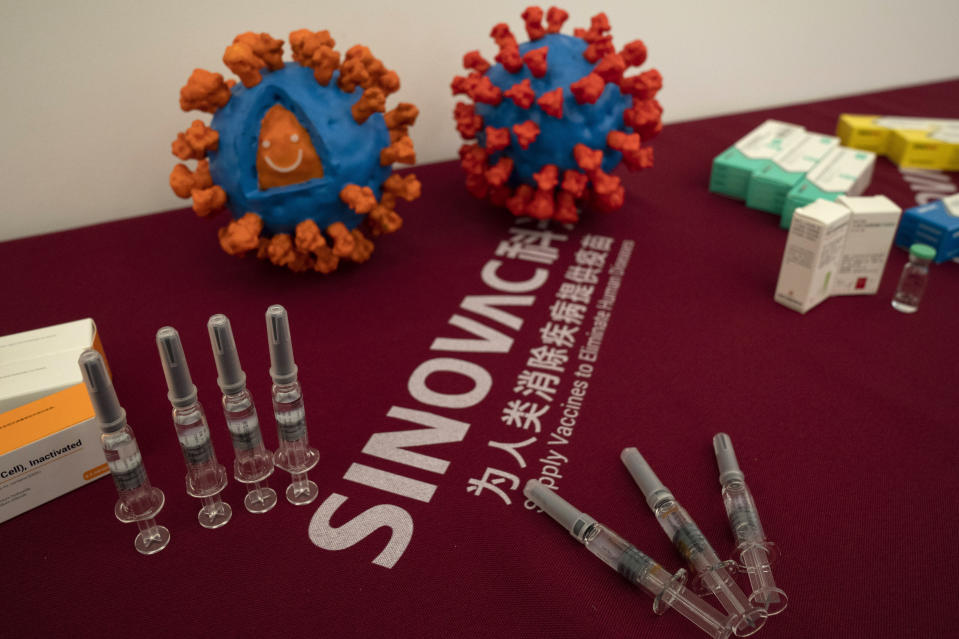 Syringes of a vaccine for COVID-19 and models depicting the coronavirus are displayed at the Sinovac factory in Beijing on Thursday, Sept. 24, 2020. (AP Photo/Ng Han Guan)