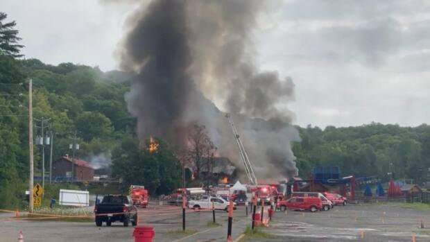 Mont Cascades waterpark says it wouldn't be safe to open while crews are sifting through debris from the fire that destroyed the resort's main chalet over the weekend. (David Bates - image credit)