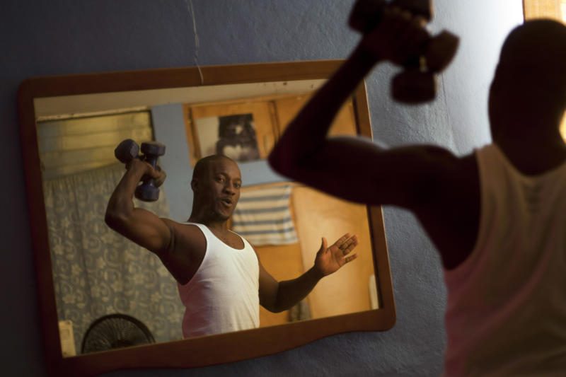 In this Jan. 18, 2013 photo, professional dancer Georges Exantus lifts weights in his bedroom in Port-au-Prince, Haiti.  Exantus thought he'd never dance again. The earthquake three years ago in Haiti's capital flattened the apartment where he was living, where he spent three days trapped under a heap of jagged rubble. After friends dug him out, doctors amputated his right leg just below the knee. Three years later, the 32-year-old professional dancer is back on the floor, spinning away as he does the salsa, cha-cha and samba. A prosthetic leg doesn't hold him back. If some see him as something of an outcast, his friends find inspiration: He's not one for self-pity; he was determined to dance again, and did. (AP Photo/Dieu Nalio Chery)
