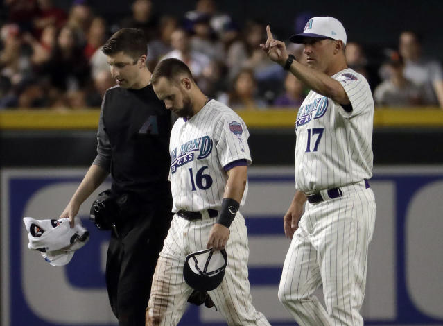 Arizona Diamondbacks manager Torey Lovullo (17) signals for a replacement during the third inning of a baseball game Thursday, April 19, 2018, in Phoenix as Chris Owings (16) leaves the game after catching a fly out hit by San Francisco Giants' Joe Panik. Owings collided with teammate A.J. Pollock after the catch. (AP Photo/Matt York)