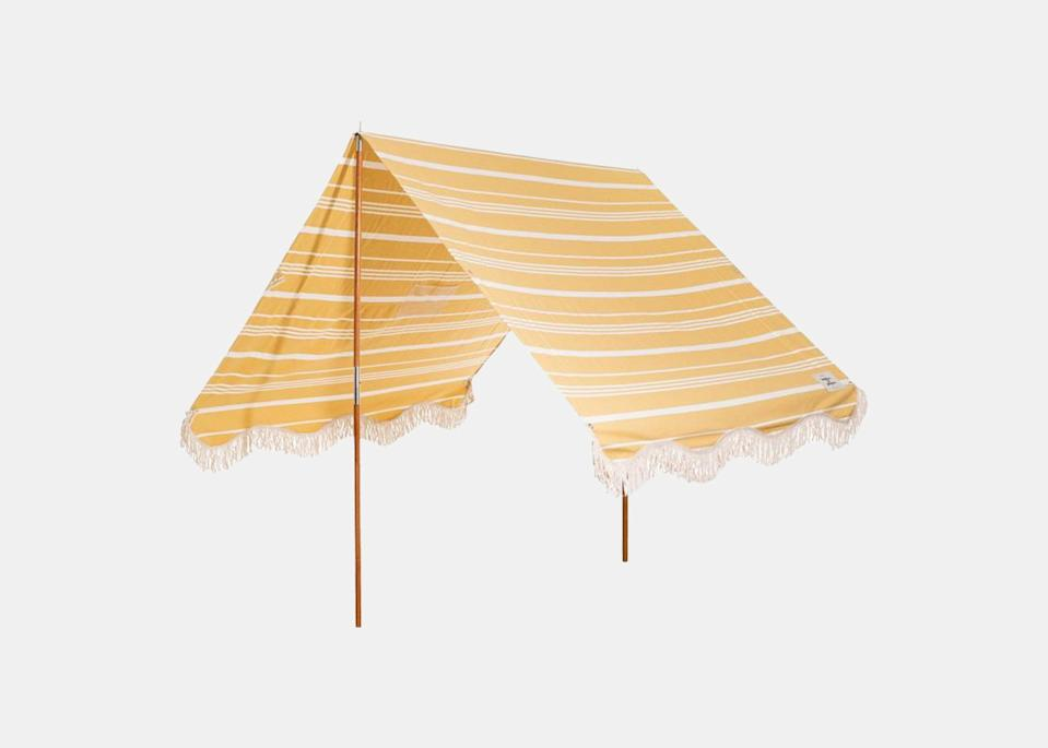 """For the family who also wants a functional, easy-to-use canopy that's as chic as the family it's shading, fashion designer <a href=""""https://www.instagram.com/theamandaperna/"""" rel=""""nofollow noopener"""" target=""""_blank"""" data-ylk=""""slk:Amanda Perna"""" class=""""link rapid-noclick-resp"""">Amanda Perna</a> recommends Business & Pleasure's beach tent, made from <a href=""""https://www.cntraveler.com/gallery/eco-friendly-gifts?mbid=synd_yahoo_rss"""" rel=""""nofollow noopener"""" target=""""_blank"""" data-ylk=""""slk:eco-friendly materials"""" class=""""link rapid-noclick-resp"""">eco-friendly materials</a>. """"I appreciate a beautiful, timeless design that elevates a functional accessory—like a beach tent—and this one delivers in so many ways,"""" says the Delray Beach, Florida, mother to four-year-old Stella. $299, West Elm. <a href=""""https://food52.com/shop/products/6180-vintage-inspired-french-riviera-beach-tents"""" rel=""""nofollow noopener"""" target=""""_blank"""" data-ylk=""""slk:Get it now!"""" class=""""link rapid-noclick-resp"""">Get it now!</a>"""