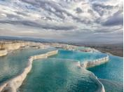 """<p>Pamukkale, which means """"cotton castle,"""" is a stack of white travertine mineral pools in southwest Turkey. The UNESCO World Heritage Site looks over the Byzantine-Roman city of Denizli.</p>"""