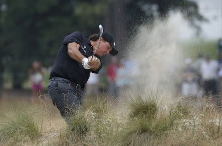 Phil Mickelson of the U.S. hits a shot from the rough on the 12th hole during the first round of the U.S. Open Championship golf tournament in Pinehurst, North Carolina, June 12, 2014. REUTERS/Mike Segar