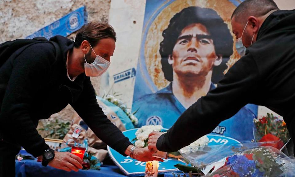 People light candles at a shrine to Diego Maradona in Naples