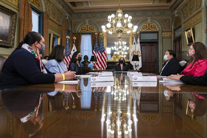At a gleaming table beneath chandeliers, people in masks sit for a meeting.