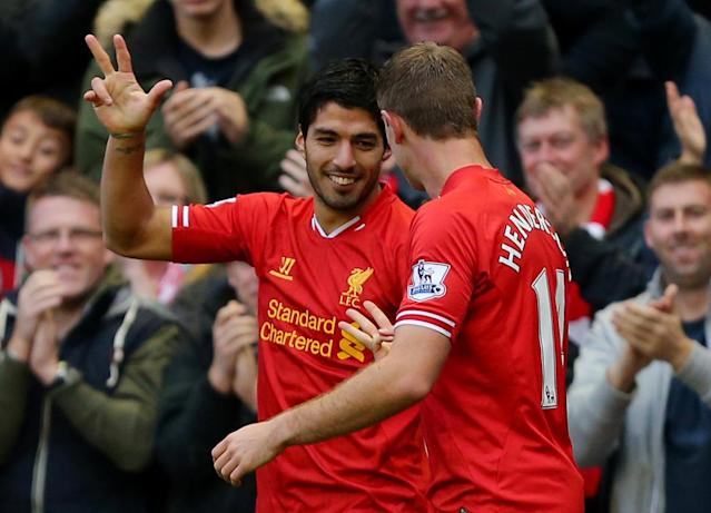 Liverpool's Luis Suarez, left, celebrates scoring his and Liverpool's third goal of the game during the English Premier League soccer match against West Bromwich Albion at Anfield, Liverpool, England, Saturday, Oct. 26, 2013. (AP Photo/Dave Thompson, PA Wire)