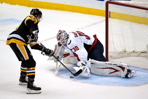 Pittsburgh Penguins' Jake Guentzel, left, puts a shot under the glove hand of Washington Capitals goaltender Ilya Samsonov (30) for a goal during a shootout in an NHL hockey game in Pittsburgh, Sunday, Jan. 17, 2021. (AP Photo/Gene J. Puskar)