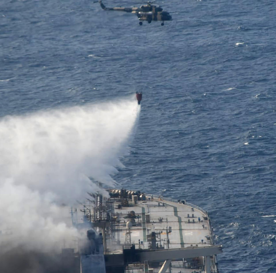 In this photo provided by Sri Lanka Air Force, a chopper helps battle the fire on MT New Diamond off the eastern coast of Sri Lanka in the Indian Ocean, Saturday, Sept. 5, 2020. The fire on the large oil tanker off Sri Lanka's coast has been brought under control but is still not extinguished, the navy said Saturday. The tanker, carrying nearly 2 million barrels of crude oil, was drifting about 20 nautical miles (37 kilometers) from Sri Lanka's eastern coast and on Friday evening a tug boat towed it to the deep sea away from land, said navy spokesman Capt. Indika de Silva. (Sri Lanka Air Force via AP)