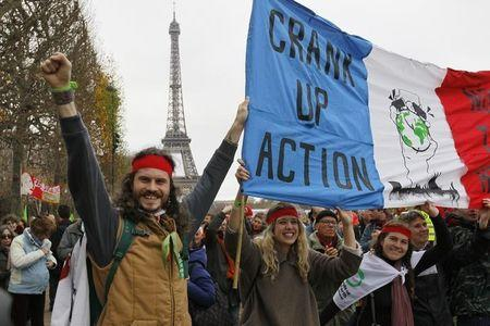 Environmentalists hold a banner at a protest demonstrationnear the Eiffel Tower in Paris, France, as the World Climate Change Conference 2015 (COP21) continues near the French capital