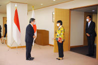 Japan's Foreign Minister Toshimitsu Motegi, left, welcomes Indonesian Foreign Minister Retno Marsudi, center, at the entrance of the meeting room prior to the Japan-Indonesia Foreign Ministers meeting in Tokyo on Monday, March 29, 2021. Indonesian Foreign Minister Retno Marsudi and Defense Minister Prabowo Subianto are in Japan from March 28-30, 2021. (David Mareuil/Pool Photo via AP)