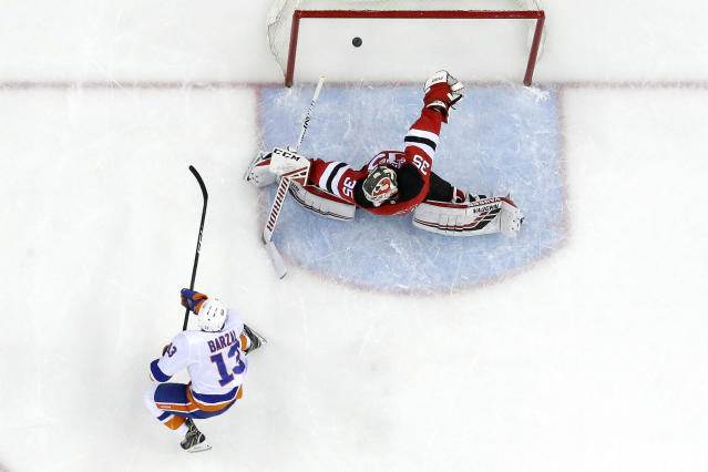 New York Islanders center Mathew Barzal (13) scores a goal on New Jersey Devils goaltender Cory Schneider (35) during the first period of an NHL hockey game Thursday, Feb. 7, 2019, in Newark, N.J. The Islanders won 2-1 in a shootout. (AP Photo/Julio Cortez)
