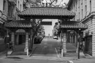 Framed by the Dragon's Gate, a woman crosses Chinatown's Grant Avenue in San Francisco on April 17, 2020. Normally, the months leading into summer bring bustling crowds to the city's famous landmarks, but this year, because of the coronavirus threat they sit empty and quiet. Some parts are like eerie ghost towns or stark scenes from a science fiction movie. (AP Photo/Eric Risberg)