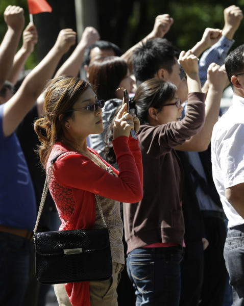 A Chinese woman uses her camera phone near protesters chant slogans outside the Japanese embassy in Beijing, China, Wednesday, Sept. 12, 2012. A territorial flare-up between China and Japan intensified as two Beijing-sent patrol ships arrived near disputed East China Sea islands in a show of anger over Tokyo's purchase of the largely barren outcroppings from their private owners. (AP Photo/Ng Han Guan)