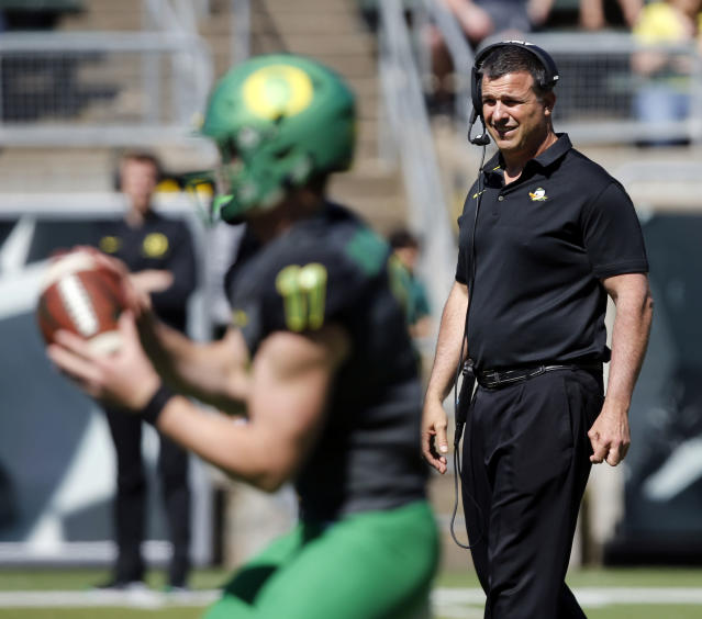 Oregon head coach Mario Cristobal, right, watches quarterback Braxton Burmeister during the Oregon spring college football game Saturday, April 21, 2018, in Eugene, Ore. (Andy Nelson/The Register-Guard via AP)