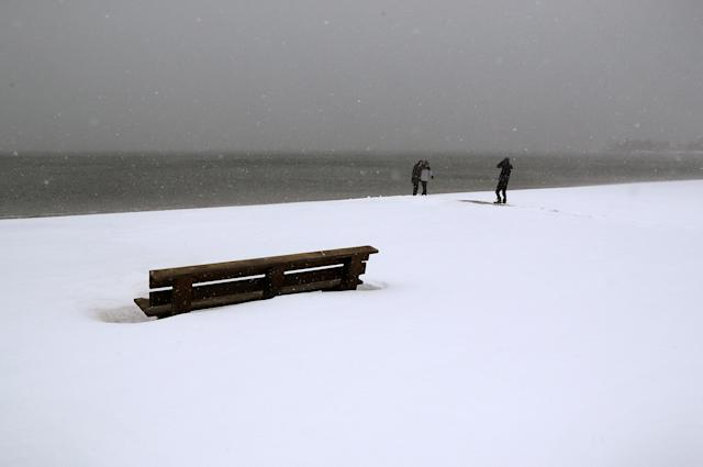 <p>People pose for photos on a snow-covered beach at the Long Island Sound on January 4, 2018 in Milford, Conn. (Photo: John Moore/Getty Images) </p>