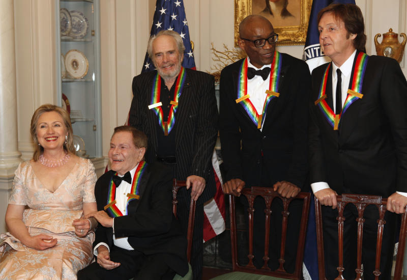 Secretary of State Hillary Clinton, left, talks with Kennedy Center honorees for 2010 Jerry Herman, Merle Haggard, Bill T. Jones, and Paul McCartney while waiting for Oprah Whitney to arrive for a group photo after at a dinner held at the State Department honoring the recipients of the Kennedy Center Honors, in Washington, on Saturday, Dec. 4, 2010. (AP Photo/Jacquelyn Martin)