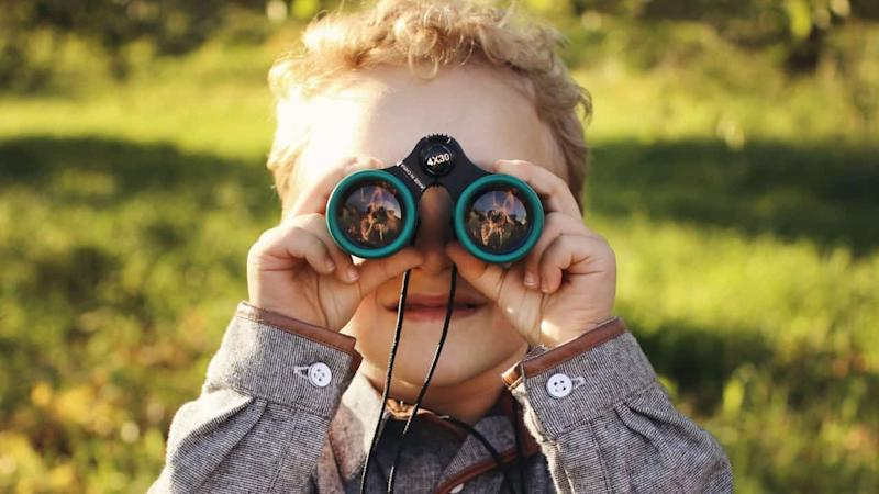 Boy with small binoculars and green field in background