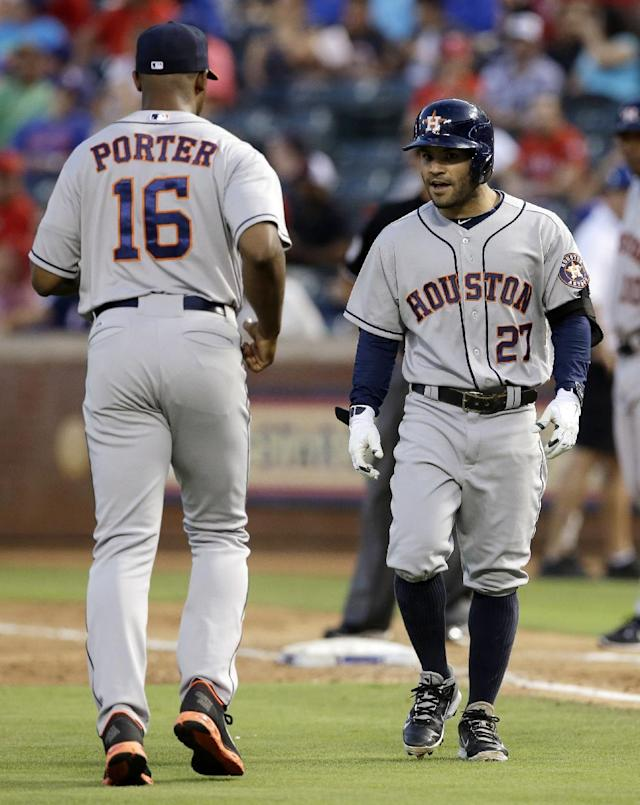 Houston Astros manager Bo Porter jogs out to first to discuss a call with umpire Vic Carapazza, rear, as Jose Altuve walks back to the dugout after being called out in the fourth inning of a baseball game against the Texas Rangers, Monday, July 7, 2014, in Arlington, Texas. The umpiring crew reversed the call after an instant replay review calling Altuve safe at first with a single to shortstop. (AP Photo/Tony Gutierrez)