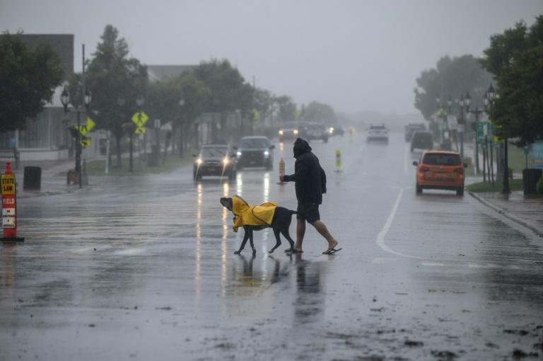 A man and dog walk cross a street before traffic as Tropical Storm Henri approaches, in Montauk, Long Island on August 22, 2021