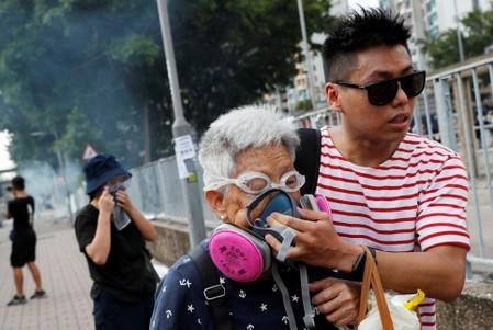 FILE PHOTO: An elderly woman is helped by a demonstrator after police fired tear gas during a demonstration in support of the city-wide strike and to call for democratic reforms at Tin Shui Wai in Hong Kong