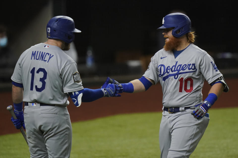 Los Angeles Dodgers' Justin Turner celebrates his home run with Max Muncy against the Tampa Bay Rays during the first inning in Game 3 of the baseball World Series Friday, Oct. 23, 2020, in Arlington, Texas. (AP Photo/Eric Gay)