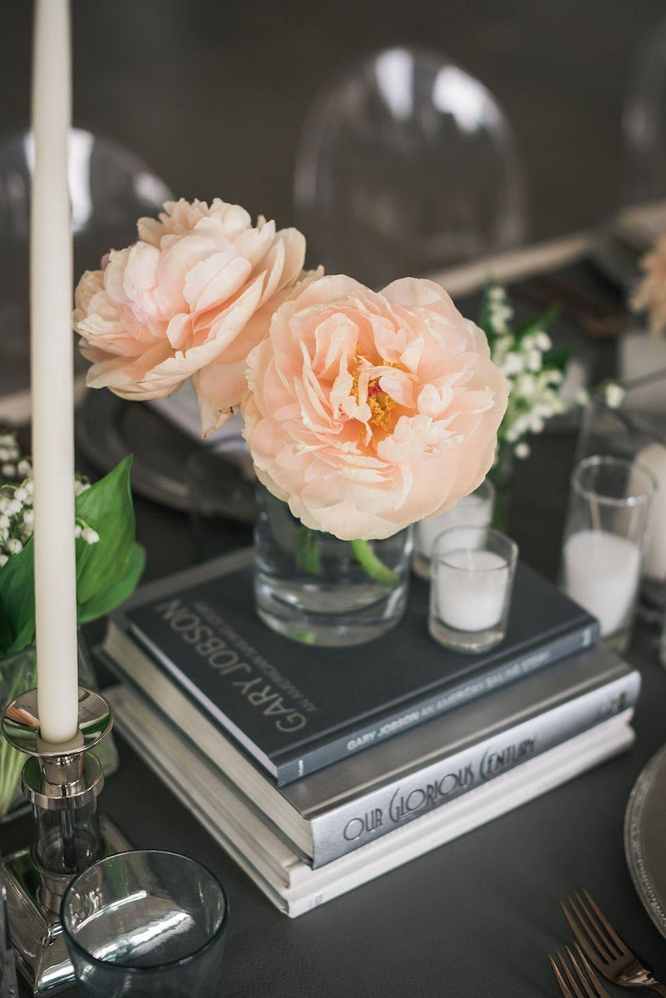 "<p>A dozen roses is the tradition, but just one or two blooms in a small vase can be equally charming (and saves space on a crowded dinner table!). Here, <a href=""https://www.elledecor.com/life-culture/g3459/rose-color-meaning/"" rel=""nofollow noopener"" target=""_blank"" data-ylk=""slk:peach roses"" class=""link rapid-noclick-resp"">peach roses</a> situated in a vase on stacked books make for a charming centerpiece. </p><p><em>Via <a href=""http://decorationinc.com/"" rel=""nofollow noopener"" target=""_blank"" data-ylk=""slk:Decoration Inc"" class=""link rapid-noclick-resp"">Decoration Inc</a></em></p><p><a class=""link rapid-noclick-resp"" href=""https://go.redirectingat.com?id=74968X1596630&url=https%3A%2F%2Fglobalrose.com%2Fflowers%2Fvday-1-dozen-peach-roses-f.html%3Fgclid%3DCj0KCQiAsvTxBRDkARIsAH4W_j9KdMlL8PiZKfhUmidkzHyDHE8Tj1WDW0IkK13OmLmGAyNPKc9iEwUaAk2_EALw_wcB&sref=https%3A%2F%2Fwww.elledecor.com%2Flife-culture%2Ffun-at-home%2Fg2387%2Fvalentines-day-decor%2F"" rel=""nofollow noopener"" target=""_blank"" data-ylk=""slk:GET THE LOOK"">GET THE LOOK</a><em><br>Peach Roses, Global Rose, $54</em></p>"