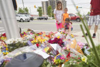 <p>Children place flowers at the scene of a hate-motivated vehicle attack in London, Ont. on Tuesday, June 8, 2021, which left four members of a family dead and sent one to hospital. THE CANADIAN PRESS/ Geoff Robins</p>