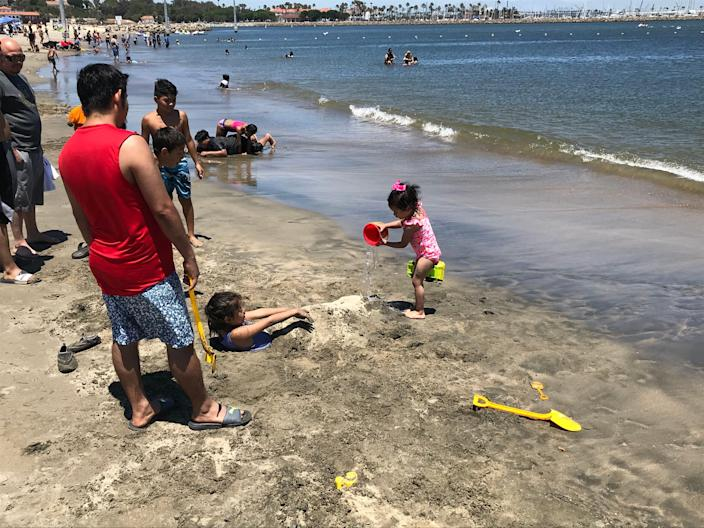 Alis Zuniga pours a bucket of seawater on her half-buried friend at Cabrillo Beach in the San Pedro section of Los Angeles. Though it is clean most days,  the beach can have high bacteria counts at certain times of year.