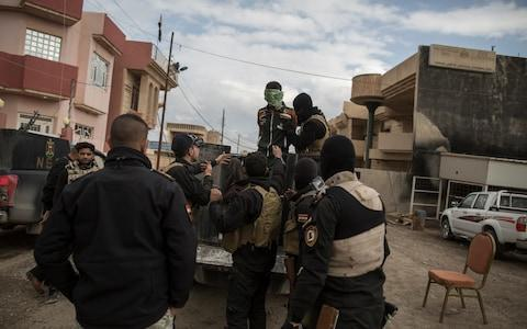 Members of the Iraqi National Security Service take a suspected Isil collaborator to their base in Bartella, near Mosul. - Credit: Sam Tarling for the Telegraph
